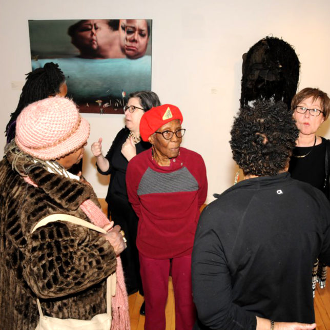 """Transitions"" co-cuator Galdys Grauer with guests at the reception. c/o Paul Robeson Galleries"