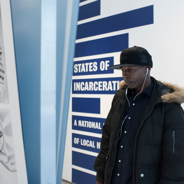 Visitor reading an exhibit panel at HAL's States of Incarceration exhibit. c/o Chris Choi