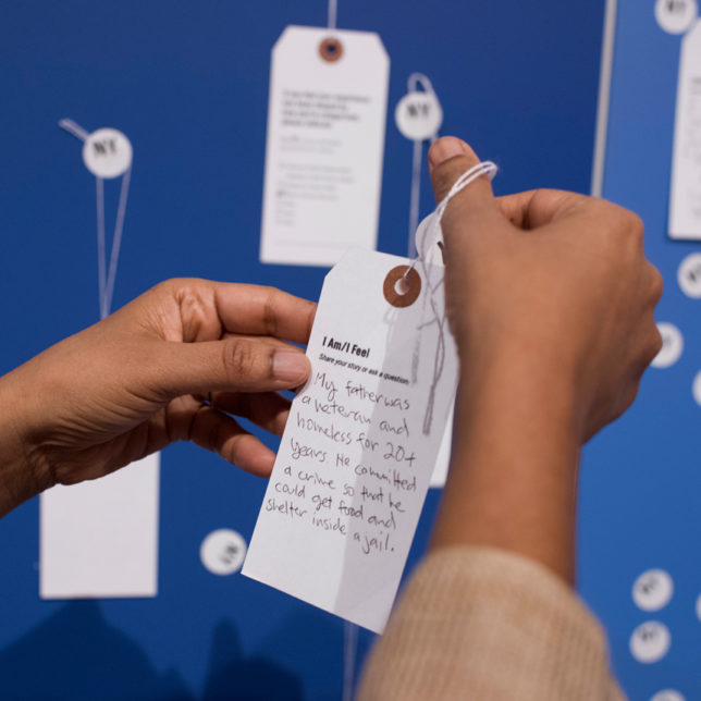 "A visitor to HAL's States of Incarceration exhibit fills out a tag for the prompt, ""How close are you to incarceration?"" c/o Chris Choi"