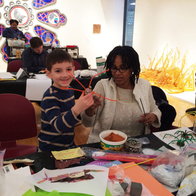 "Artist educator Adrienne Wheeler works with a child during an artmaking workshop based on the exhibition ""The Undesirables"". c/o Paul Robeson Galleries"