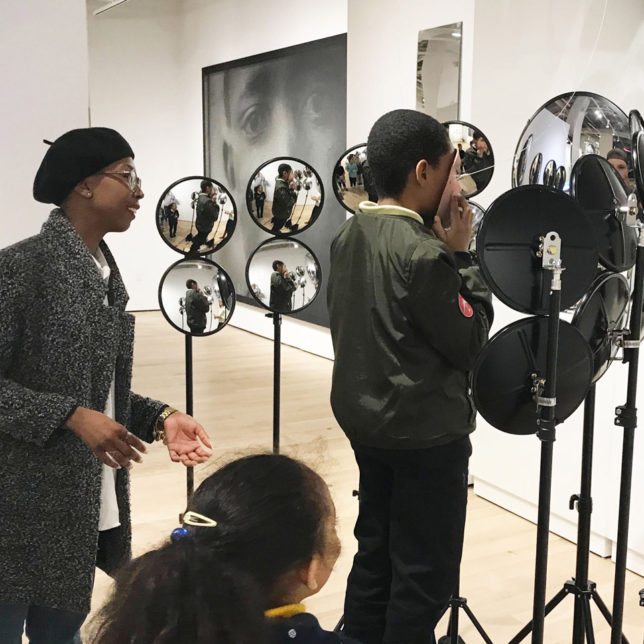 Programs Assistant Kristen Owens helps students engage with an interactive artwork by Leo Selvaggio during a Looking Lens arts education workshop. c/o Duda Penteado