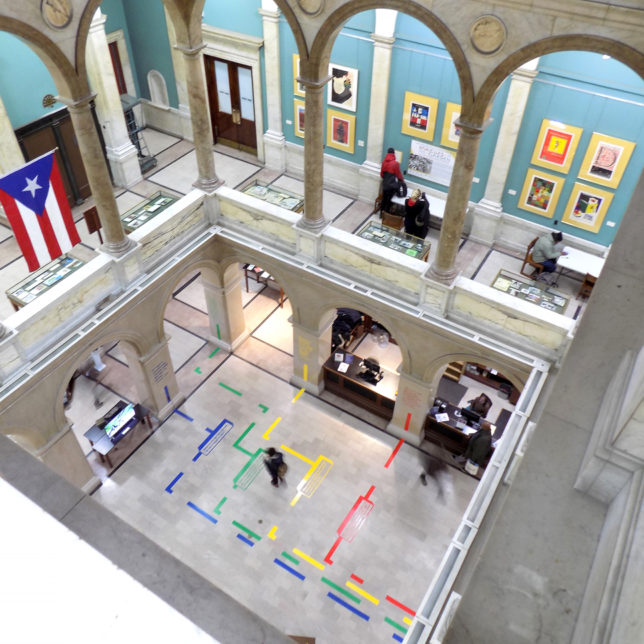 """At Home In Newark"" Exhibition's directional graphics, seen from above at the Newark Public Library. Fall 2017. (Students: Cindy Guzman, Faith Koh, Ronald Mendoza, Pamela Molina & Roshani Pise). c/o Visual Means"