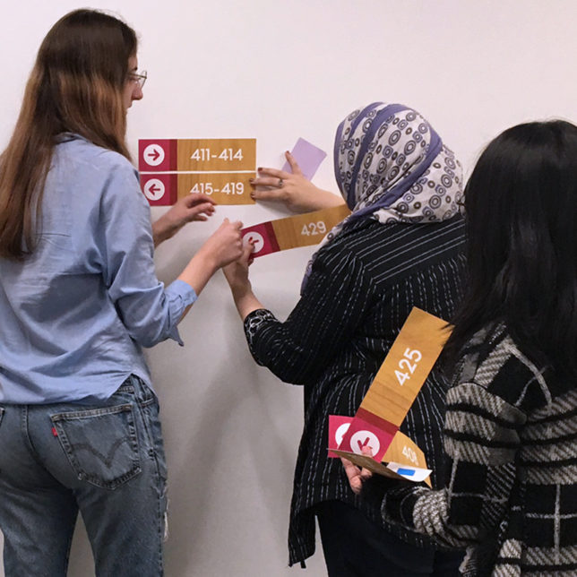 Students Marsha Shnayder, Tinhinahe Khelifi, and Sarah Barcelos testing Express Newark signage solutions. c/o Design Consortium