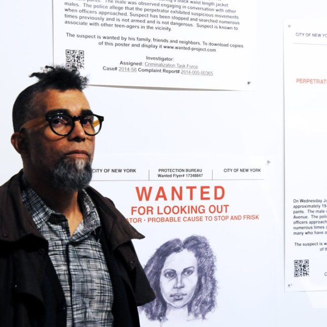 "Dread Scott with his work, ""Wanted"" 2014, a community based project consisting of offset prints, performance, video, website, inkjet prints, forums, community participants, developed collaboratively with No Longer Empty, The Stop Mass Incarceration Network and young adults in Harlem. The sketches were drawn by Kevin Blythe Sampson. c/o the artist."