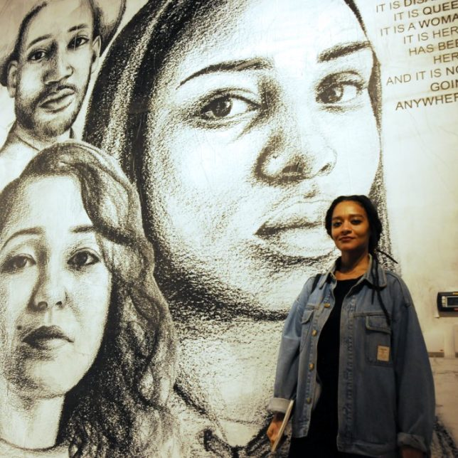 "Tatyana Fazlalizadeh with her work ""America is Black,"" 2018, wheat paste installation. c/o of the artist"