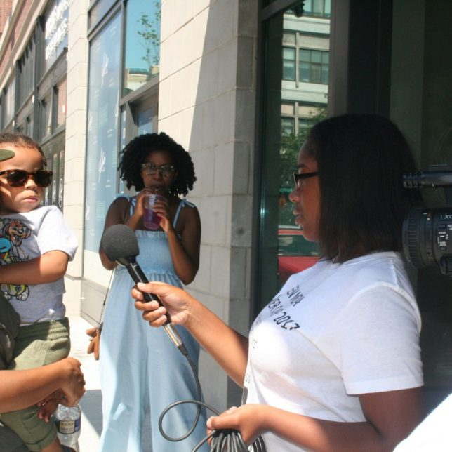 Campers interviewing passers bye, as they learn how to conduct an interview in front of a camera. c/o Kadijah Taylor