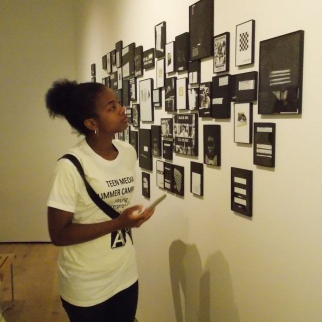 One of the Campers taking a look inside The Box, exhibition at Express Newark. c/o Community Media Center.