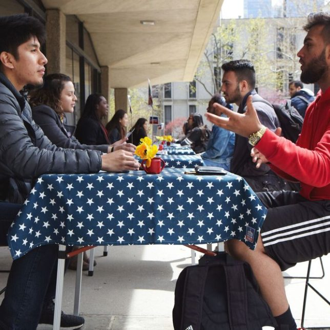 Carlos, a RU-N student facilitating a discussion on Immigration at a Ten Table event. With 5 minutes each, conversations are guided by questions aiming to break down political divides by understanding where our beliefs come from. This event is modeled after the documentary film Bring it to the Table, directed by Julie Winokur. — withTalking Eyes Media and Bring It to The Table at Rutgers University—Newark. c/o Newest Americans