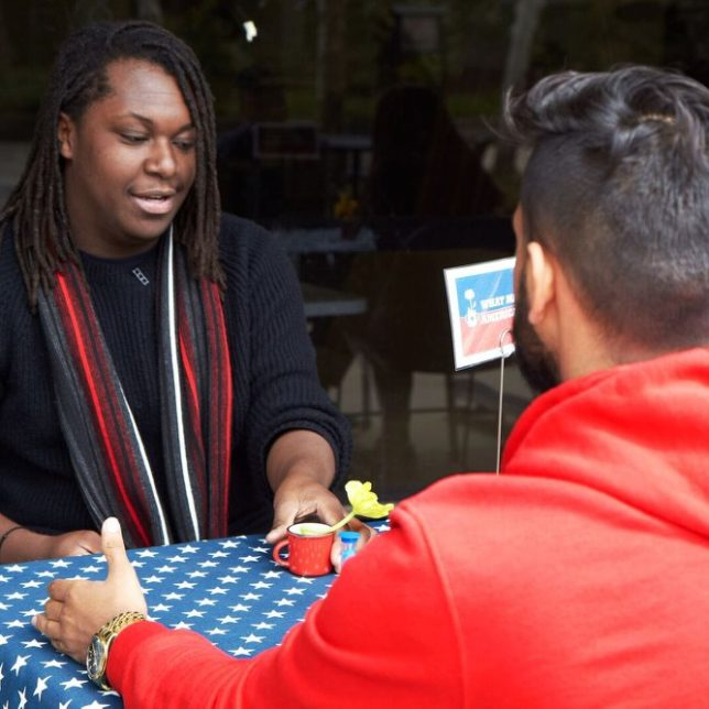 Rutgers University-Newark Senior, Dylan Brown facilitating a conversation about What Makes America Great? The Ten Table event concept was dervived from the documentary film Bring it to the Table, which explores how political conversations can bridge divides through open dialog. Bring it to the Table is as much about listening as it is about politics, perspectives and personal reflexes. — at Rutgers University—Newark. c/o Newest Americans