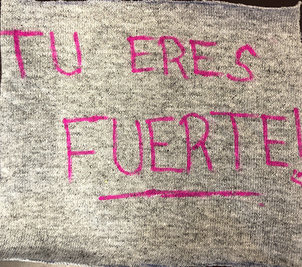 "The words, ""Tu eres fuert!"" written in pink marker on a light grey square of fabric."