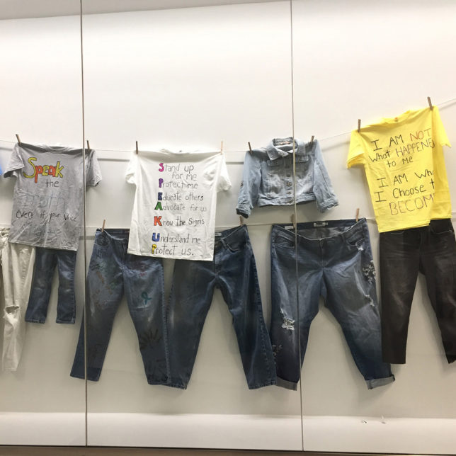 A row of t-shirts, covered in hand written text, hung on a clothesline. A row of blue jeans hangs from a clothesline below the t-shirts.