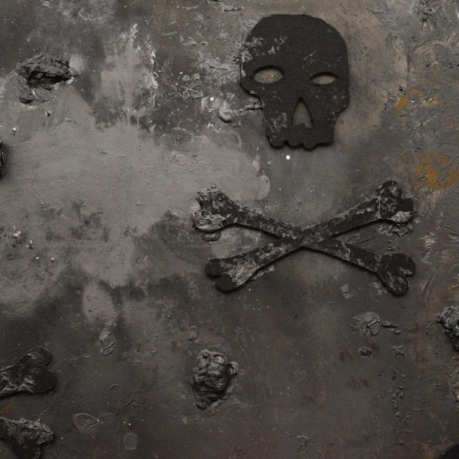 Detail of a dark grey, textured painting with a skull and crossbones