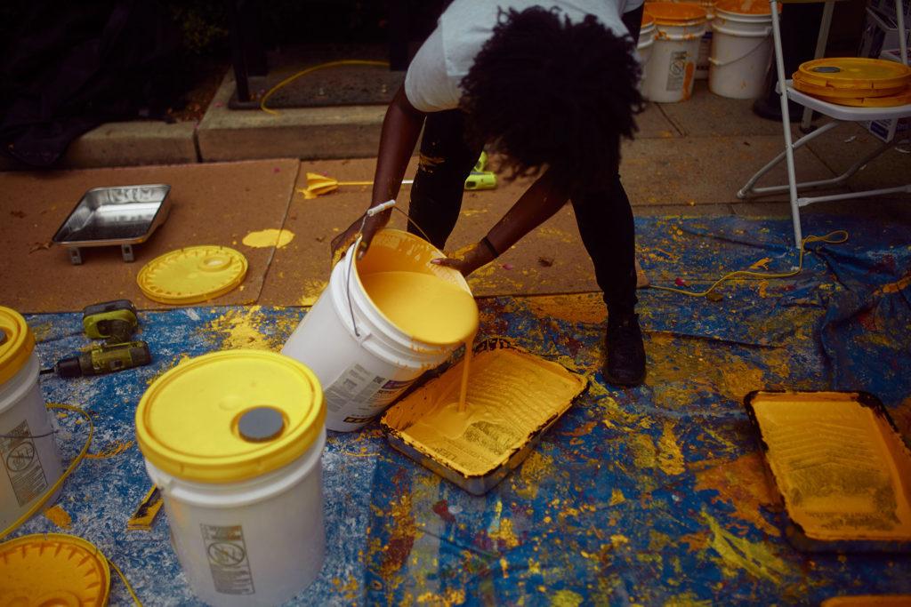 Alumni Tiffany Hale leads paint distribution. c/o Redens Desrosiers